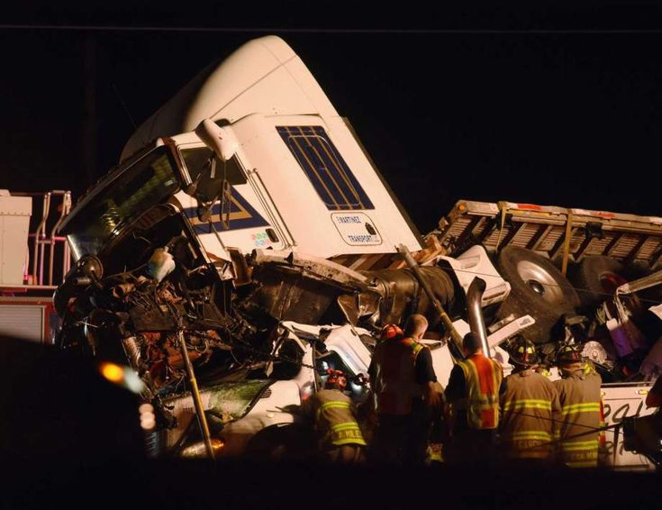 A tractor trailer rests atop a vehicle on Interstate 35 South at Somerset Road on San Antonio on Wednesday, Nov. 29, 2017. One person is known dead in the accident. Photo: Billy Calzada, San Antonio Express-News / San Antonio Express-News
