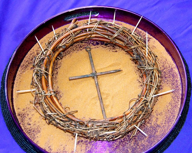 Lent decorations.  Purple tray for liturgical time, sand for 40 days in the dessert, crown of thorns and cross made of nails.