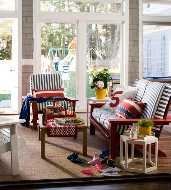 A four-season porch design for casual entertaining is enhanced by equally casual furnishings. Adirondack chairs are an always-welcome classic, perfect for lounging. In this space, the design was adapted into a sofa, which easily accommodates two people. An infusion of red, white, and blue in striped motifs creates a nautical look that exudes summer style.