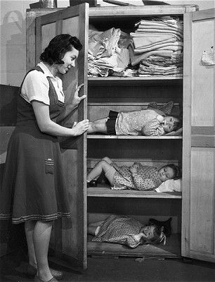 Cupboard Shelter, December 1943. A day nursery in the East End of London shelters children in a linen cupboard during an air raid. Some homes had Morrison shelters – a steel table with wire mesh sides - where they took cover during raids whilst others put up Anderson shelters in their gardens. Regular practices were held and schoolchildren were drilled in the use of gas masks.