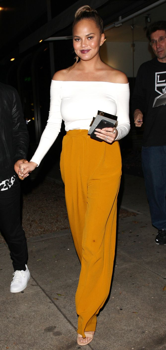 Chrissy Teigen in a cream off-the-shoulder top and yellow pants