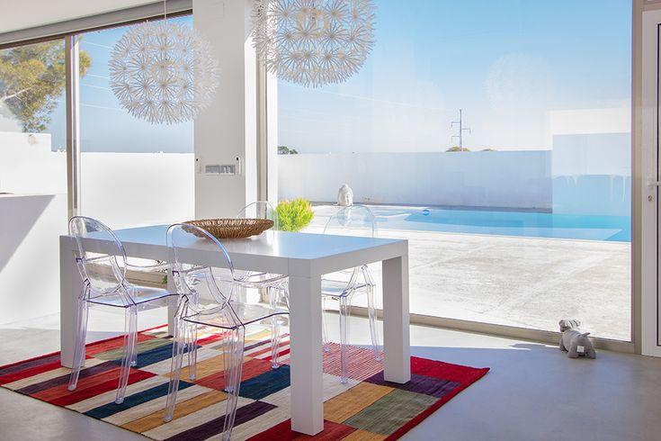 Chiralt Arquitectos I Mobiliario de comedor con impresionantes vistas a terraza con piscina en vivienda moderna.