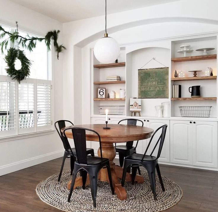 table and chairs with rug. styled, built-in shelving