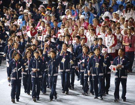 日の丸や英国旗を手に入場する日本選手ら=12日、五輪スタジアム(共同)