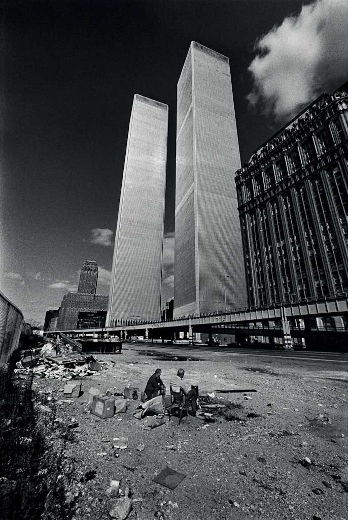 Manhattan, New York City, New York / October, 1975 Two homeless men squat in the shadow of the recently completed World Trade Center. New York City was on the verge of bankruptcy and the World Trade Center sat largely vacant, unable to find companies to fill its large office spaces.