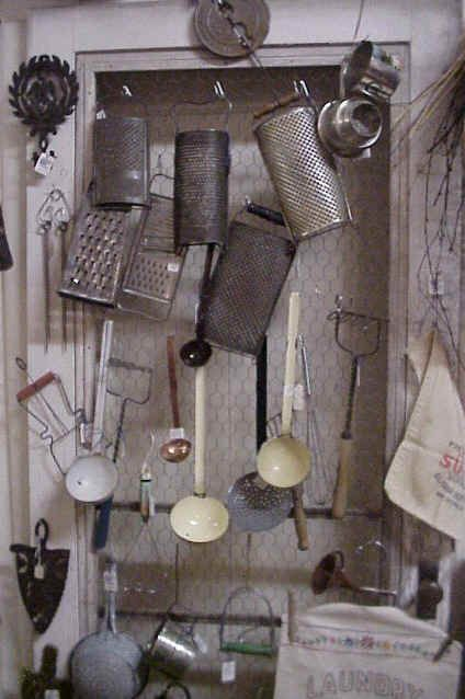 vintage kitchenware hanging on hooks  an old window covered in chicken wire