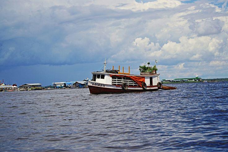 Barco de madeira,  em frente  ao   rio Negro, Manaus.
