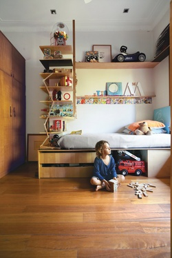 Tom's compact bedroom feels much larger thanks to interlocking shelves and storage. The plywood bed and surrounding shelv­ing were custom-built by Wilkin and a hired carpenter.