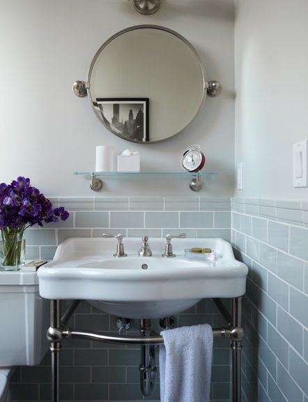 Beautiful Vintage Inspired Bathroom With Soft Gray Subway Tile White Porcelain Console Sink Round Mirror And Glass Shelf