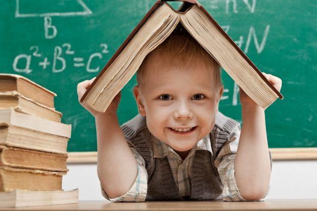 młody chłopiec trzymający książkę nad głową w klasie szkolnej