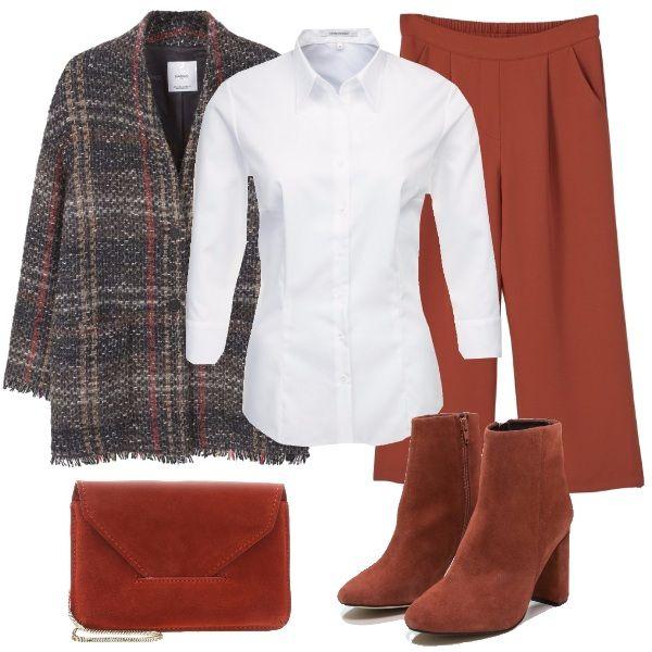 La classica camicia bianca è indossata con abbigliamento ed accessori marroni. Il cappottino a scacchi si abbina ai pantaloni cropped a vita alta, agli stivaletti dal tacco comodo e alla piccola tracolla in tinta.