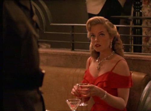 White Mischief (1987) - Greta Scacchi as Lady Diana Broughton wearing a red silk evening dress with off-shoulder neckline and ruffles on the bodice. The accessories include diamond jewellery. The costumes were designed by Marit Allen.