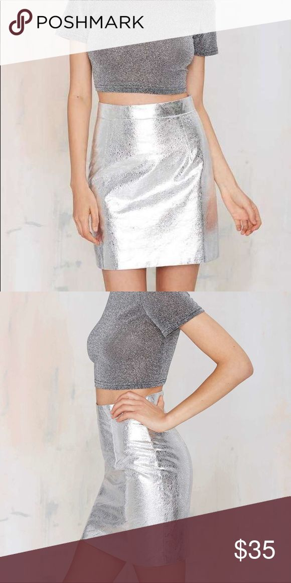 """Nasty Gal Space Cowgirl metallic silver mini skirt Become out of this world with this one of a kind silver metallic high waist mini skirt by Nasty Gal.  Soar into Spring season with this must have piece.   Fully lined with soft, silky material.  6.5"""" silver zipper down back side   Measurements are approximate (flat lay): Waist- 15"""" Hips- 19.5"""" Length- 17.5""""  60% cotton 40% polyester   Size Medium Glamorous by Nasty Gal  NWT Nasty Gal Skirts Mini"""