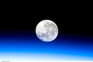 A full moon is visible in this view above Earth's horizon and airglow, photographed by Expedition 10 - Commander Leroy Chiao on the International Space Station. - The last for the year.