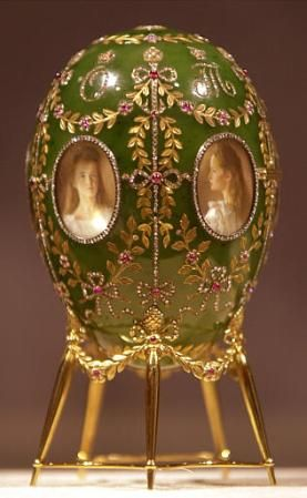 1/2 The 1908 Alexander Palace Egg is made of Siberian nephrite, diamonds, gold, rubies & miniature watercolor paintings on ivory. The outside of the egg contains five miniature watercolor portraits of the children of Nicholas II and Alexandra:  Above each portrait is a diamond monogrammed initial of each child's first name  The remainder of the egg's surface is divided by five vertical lines, studded with diamonds and connected with one another by gold garlands inlaid with rose and ruby…