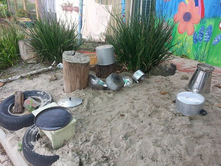 """Tyres, tree stumps & pots & pans in the sand area outdoors at Korrumburra Kindergarten - image shared by Journey into Play ("""",)"""