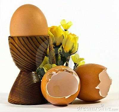Empty egg shells and an egg in a wooden egg cup with silk flowers.
