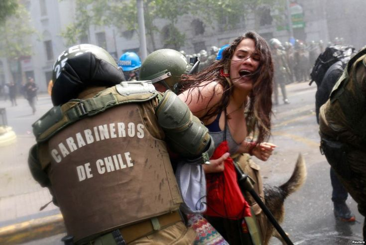 October 9, 2017:  A demonstrator is detained by riot police during a rally against Columbus Day in downtown Santiago, Chile, Oct. 9, 2017.