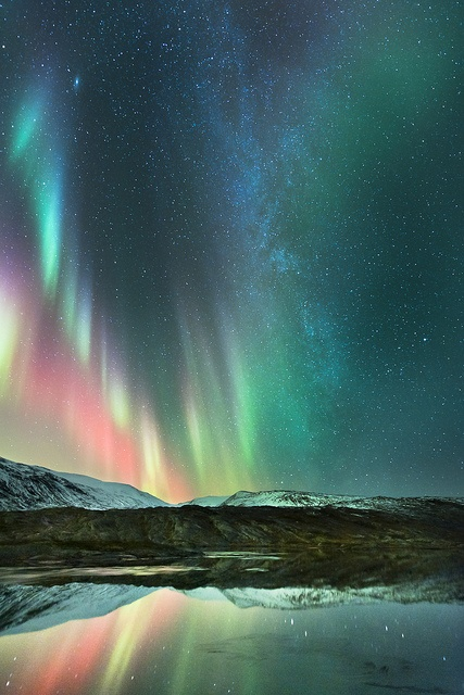 Aurora borealis and the Milky Way over Melfjellet, Norway. The Andromeda Galaxy is the larger, bright object in the upper left of the photo. Photo credit: Tommy Eliassen.