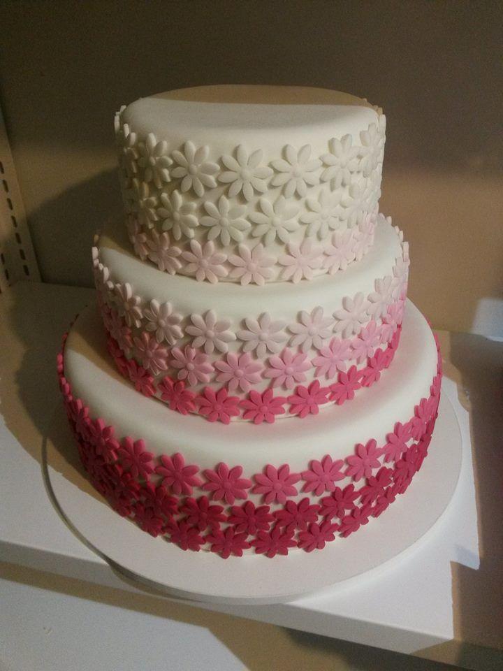 Svatební dort ozdobený odstínovanými růžovými kytičkami.