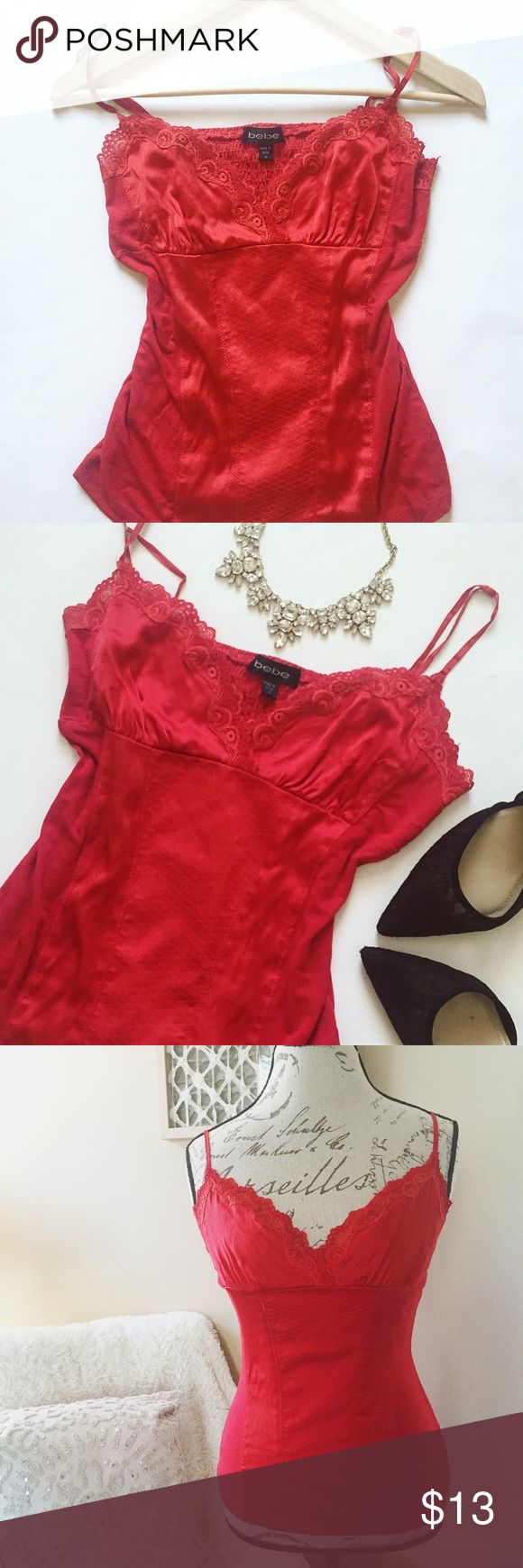 """Bebe Silk Camisole Bebe lace and silk camisole in Rio Red! Looks gorgeous on its own,or with a white or black blazer! Size M,chest measures approx 13"""",with approx 18"""" length. Made of 95% silk/5% spandex,and the contrast is 95% rayon/5% spandex,so there is some stretch to it! I would say this is in good condition,no major flaws,just a couple small white spots(see last pic) that are barely noticeable,light pilling on contrast,and right strap has part of adjuster missing,so it is a little…"""
