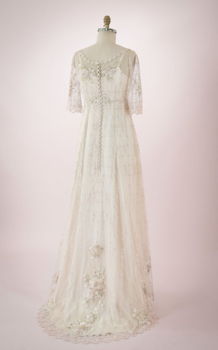 Claire by Martin McCrea | Wedding dress of delicate embroidered netting with a flower-and-vine design and embroidered appliqués over a double silk satin slip dress. Empire waist and mid-length sleeves. Optional sweeping train in the back. Available in plus size and custom sizes.