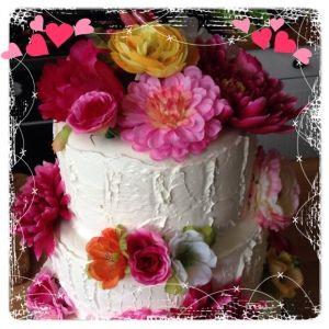 Extra hoge bruidstaart met stofe bloemen en ruwe afwerking