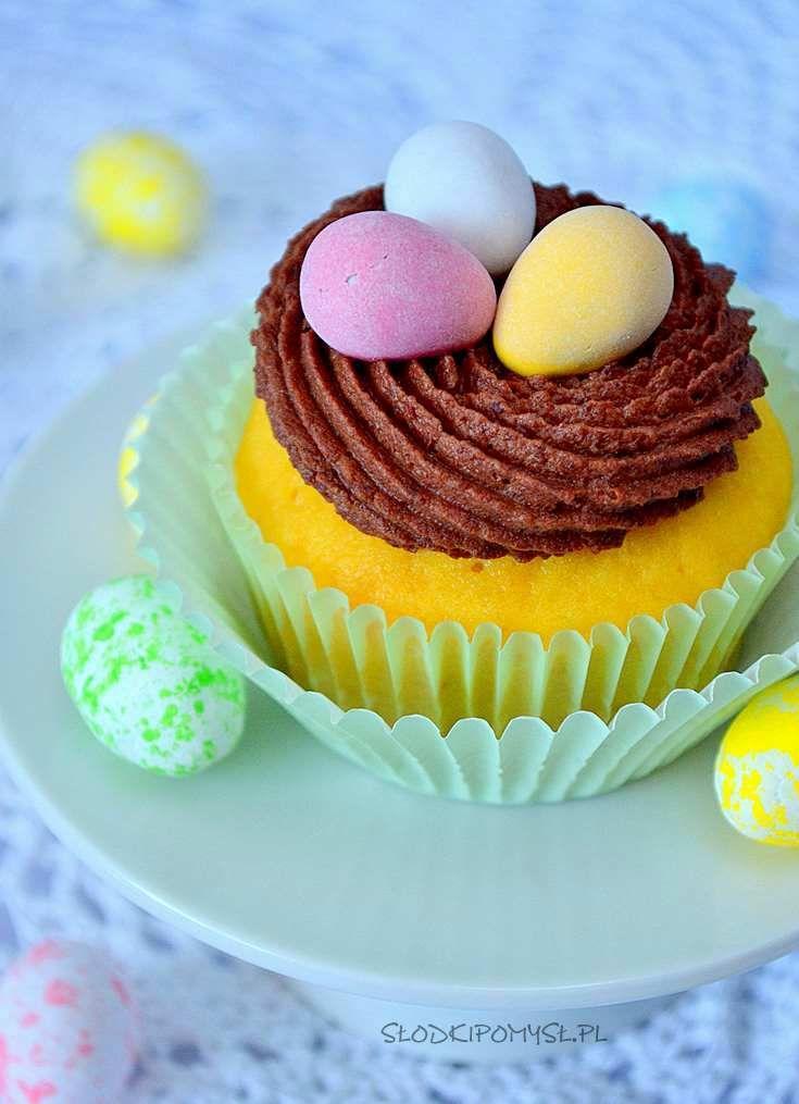 Babeczki cytrynowe z kremem czekoladowym na Wielkanoc. Przepyszne babeczki cytrynowe zostały nasączone sokiem cytrynowym i udekorowane czekoladowym kremem i kolorowymi mini jajeczkami.
