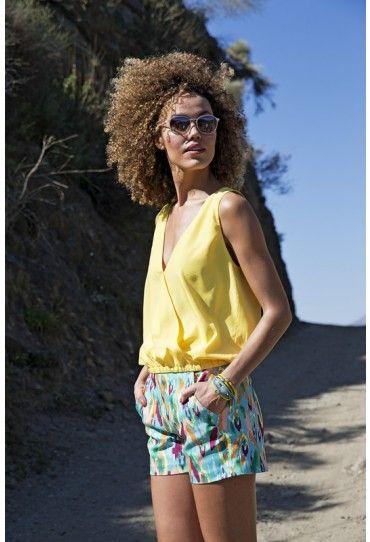 Deze top van gele polyester staat prachtig bij een zongebruinde huid. Het overslagmodel heeft elastiek in de taille en achter een halssplit met knoopje.