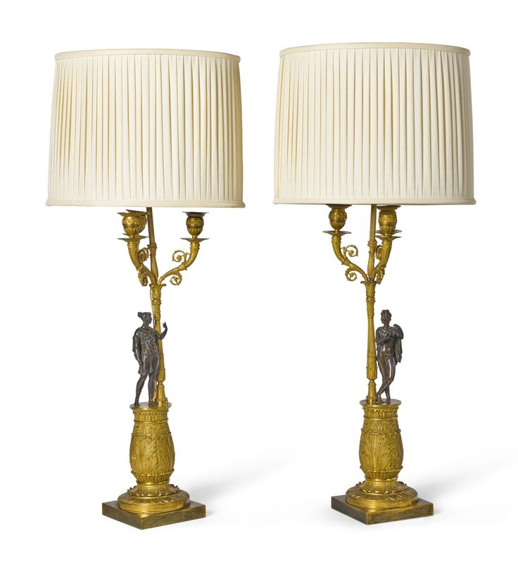 A pair of Empire style bronze and gilt-bronze candelabra early 19th century with three upturned branches arranged around an adapted central stem, on foliate slender baluster stems attended by standing figures on leaf cast baluster socles and square feet, adapted as lamps 51cm. high