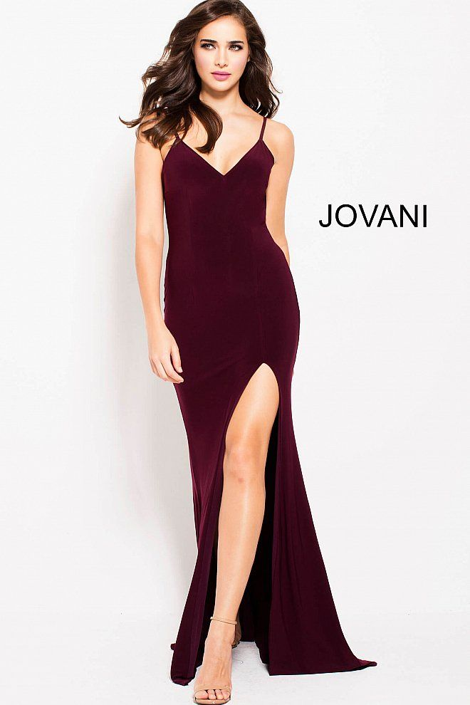 cf1c4ce5577 Floor length form fitting burgundy jersey prom dress with high slit  features sleeveless bodice with spaghetti straps v neck and low back.