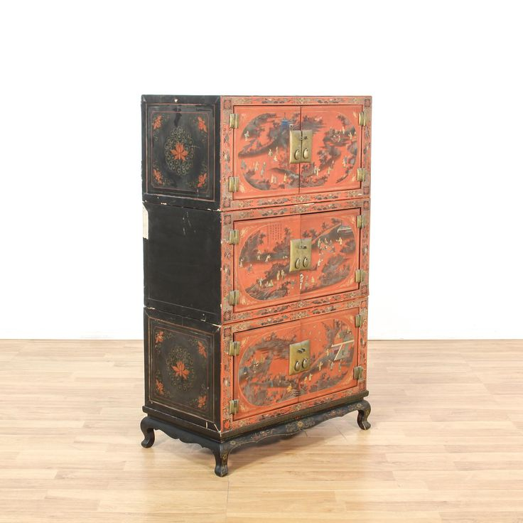 This ornate asian tansu chest is featured in a solid wood with a stunning black and red finish in hand painted chinoiserie scene details. This 3 part cabinet has shiny brass hardware, a carved base and 3 cabinet interiors. Eye catching storage piece perfect for decorating a room! #asian #storage #cabinet #sandiegovintage #vintagefurniture