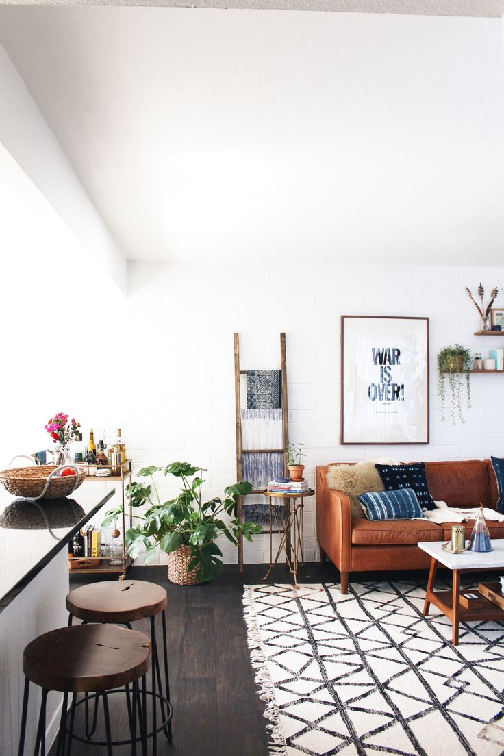 At Home with New Darlings // West Elm couch, coffee table, rug // Indigo and mudcloth pillows // War is over print // Live edge stools // Boho ethnic modern living room design