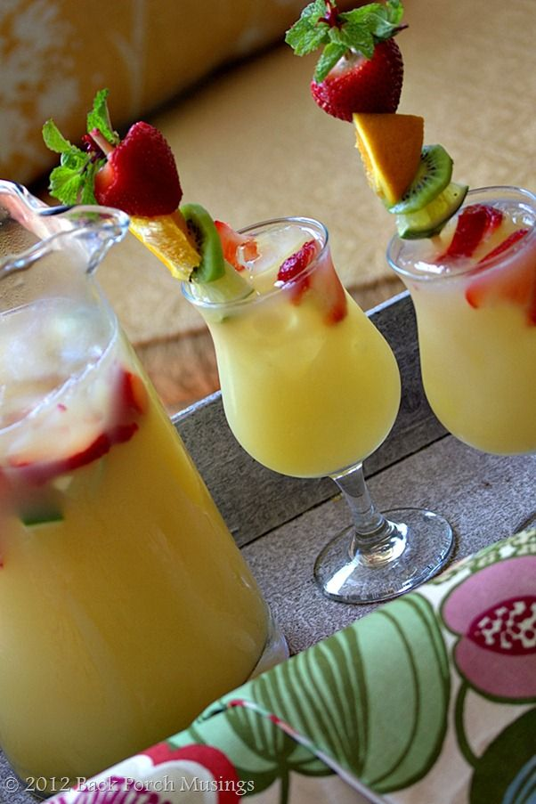 Pimeapple Strawberry Cooler: 1 12 oz. can frozen pineapple juice, thawed, 1 6 oz. frozen limeade, thawed, 4 cups cold water, 1 liter club soda, Sliced strawberries