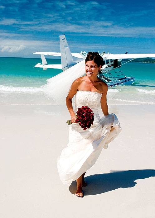 A bride alights from an Air Whitsundays plane on Whitehaven Beach; hows that for an entrance?