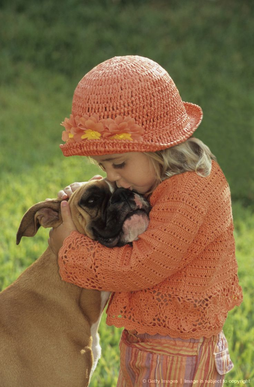 Girl (2-4) kissing boxer dog on nose, side view (Digital Enhancement)