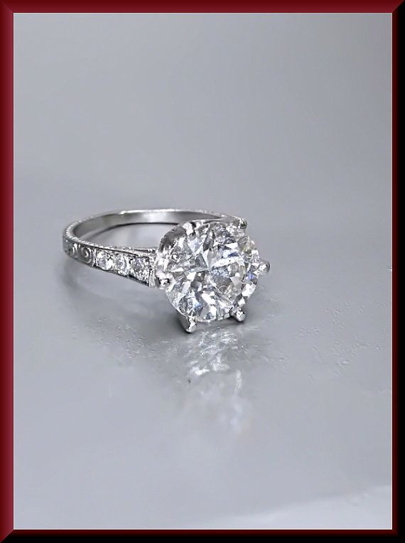 This paramount piece of art deco history is set in platinum and holds a commanding 2.55 ct old European cut diamond that has a K color and a