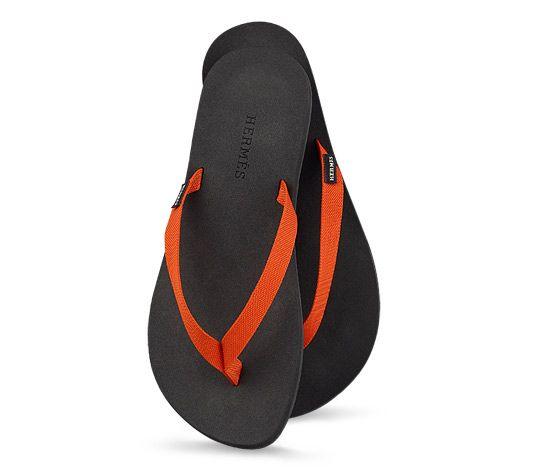 Hermès - Isolella Herrensandalen, technisches Band mit H-Druck in Orange, schwarze Gummisohle mit schwarzem Schaum, geliefert mit einem orangefarbenen Netz Ref. H041131ZHIB430 270,00 €