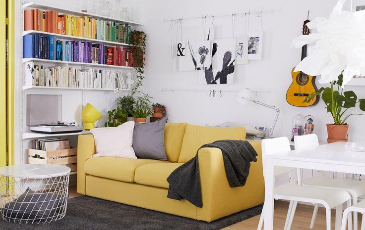 Libri dai colori sgargianti catturano lo sguardo in un soggiorno arredato su toni bianchi e gialli. Un tavolo bianco e alcuni dipinti appesi alle pareti completano l'arredo - IKEA