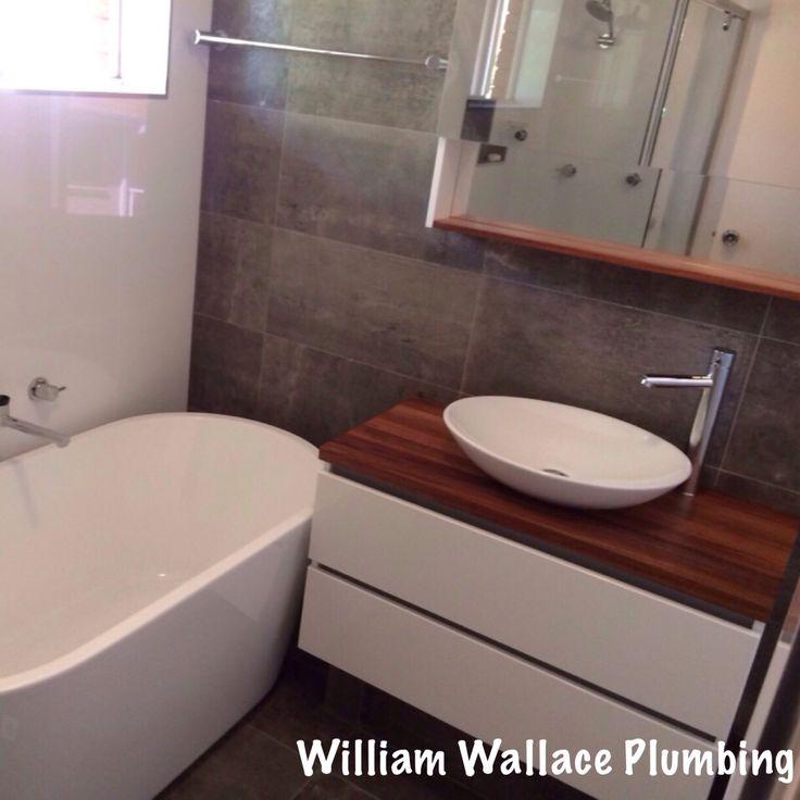 Cronulla unit bathroom renovation with timber vanity and freestanding bath.