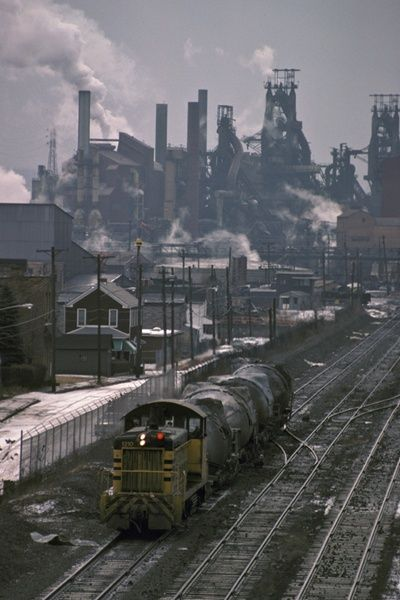 The epitome of industrial America: blast furnaces rise above workers' homes on Jan. 29, 1984, as an Aliquippa & Southern switcher brings a load of hot metal to the basic oxygen furnaces of J&L Steel in Aliquippa, Pa. The iron in these bottle cars will be converted to steel at the BOF shop and cast into ingots or billets.