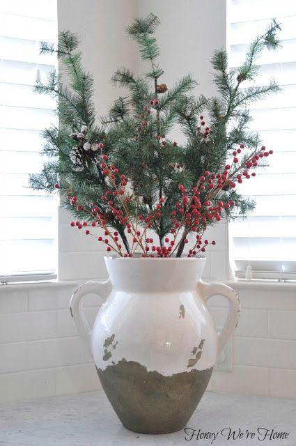 Faux pine branches and berries inside a large urn or vase make for festive holiday decor via Honey We're Home