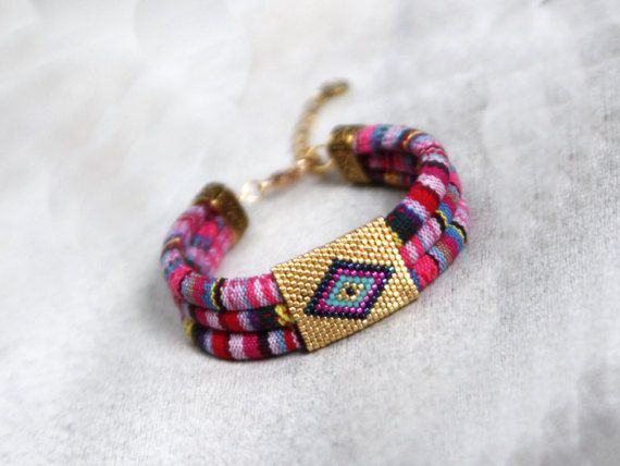 Bohemian hippie bracelet, Ibiza style bracelet - with trendy ethnic pattern. An eye-catching, statement accessory that will make you stand-out and enhance your casual outfit.  The bracelet features a beadwoven tube in golden color with a colorful, ethnic motif. Closure is a lobster clasp in golden color.  The bracelets size is 7 inches (18 cm). The small extension chain has been added also to adjust to a loose or snug fit (additional 2 inches in length). If you want a different size, please…