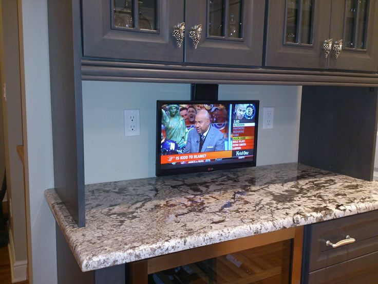 this tv is hanging from a motorized dropdown mount with the touch of a button it will retract into the cabinet above and leave you with plenty of room