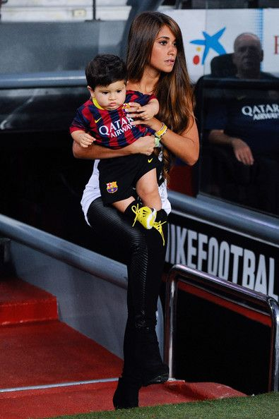 Antonella Roccuzzo and her son Thiago Messi walk onto the pitch prior to the La Liga match between FC Barcelona and Real Sociedad de Futbol at Camp Nou on September 24, 2013 in Barcelona, Catalonia.
