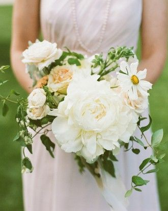 Bridesmaids clutched pale bouquets of a single large peony, roses, cosmos, and clematis vine.