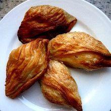 La photographie couleur présente une assiette blanche garnie de quatre pastizzi rôtis. Les stries apparentes montrent bien qu'il s'agit de pâte feuilletée.