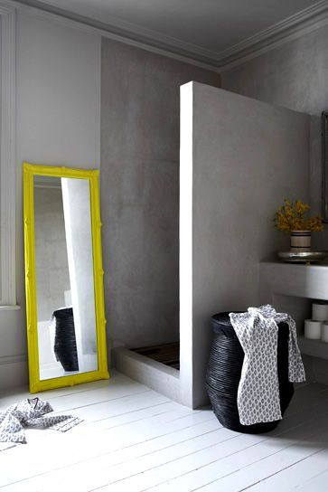 a minimalist concrete shower punched with a yellow floor mirror