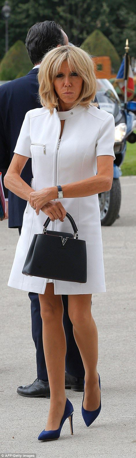 Gallic chic: Brigitte Macron, 64, was in white with blue heels for the welcoming duties. S...