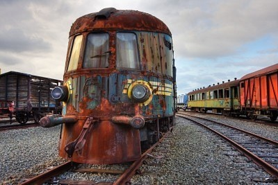Abandoned railroad engine and carriages standing on rusty rails.